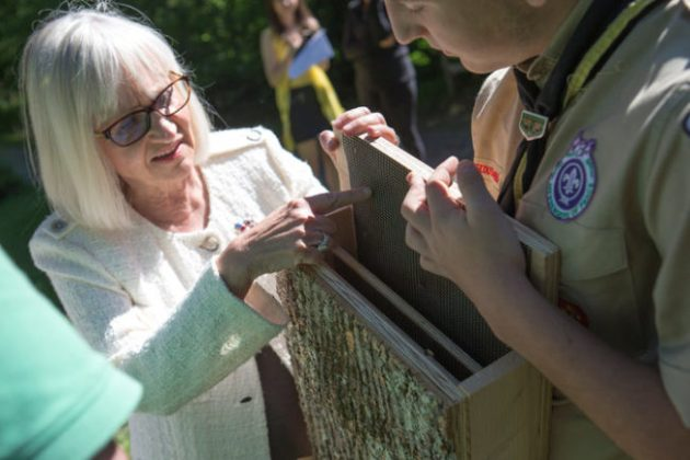 Judi Bosworth, the town supervisor, talking with Yianni Biniaris, 16, about a bat box at the botanic garden, which is home to about 20 of the houses. Photo Credit: Santiago Mejia/The New York Times