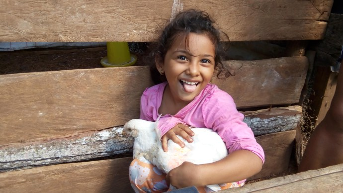 Young girl holds hen
