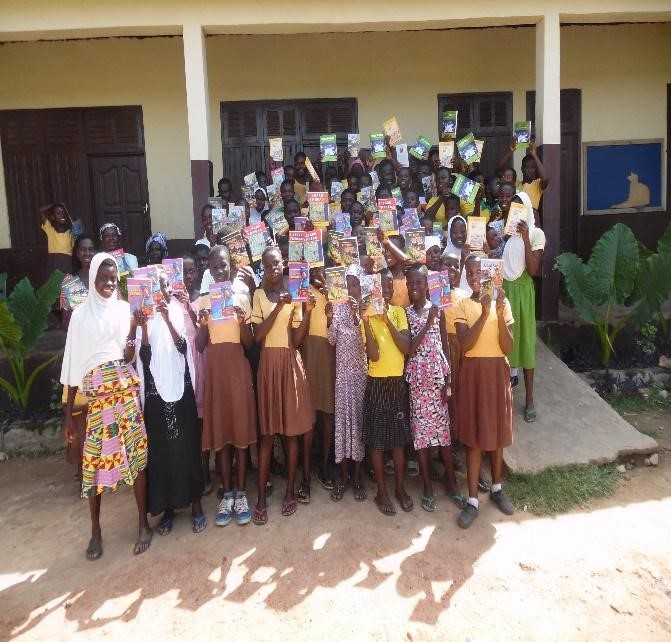 a group of teen girls pose infront of their school with their books
