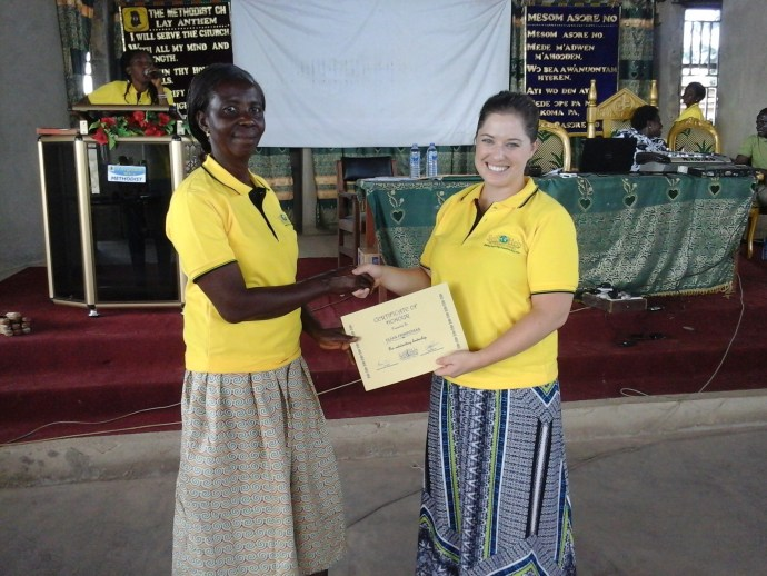 a young woman, Olivia is awarded a certificate for her hard work form SHI's executive director, Nora Tobin