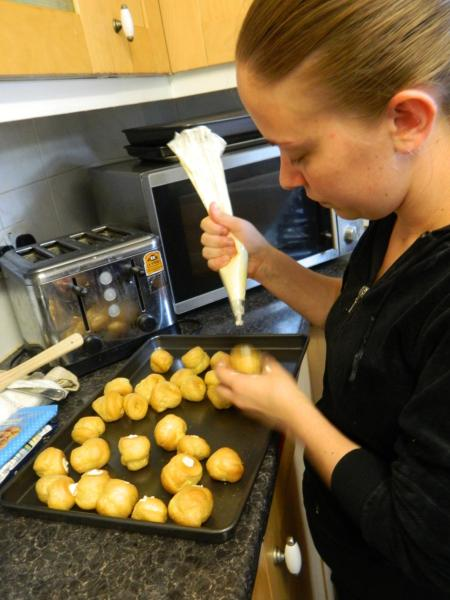 Stacey stuffing cream on the choux mini buns Photo by PH Morton