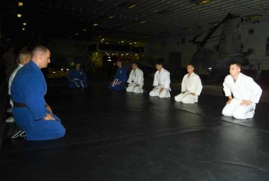 Members of the USS Nassau Judo class prepare mentally before their workout session begins.