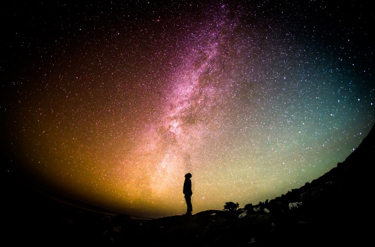 A person looking up to a starry night sky, wondering about the secrets of the universe and existence itself.