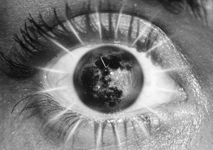 Close up image of a human eye where the colored part has been replaced by the earth. Black and white.
