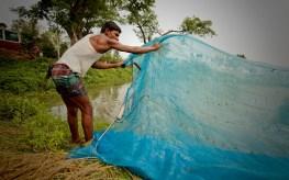 A man in Bangladesh prepares fishing nets.