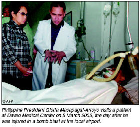 Philippine President Gloria Macapagal-Arroyo visits a patient at Davao Medical Center on 5 March 2003, the day after he was injured in a bomb blast at the local airport. [AFP photo]