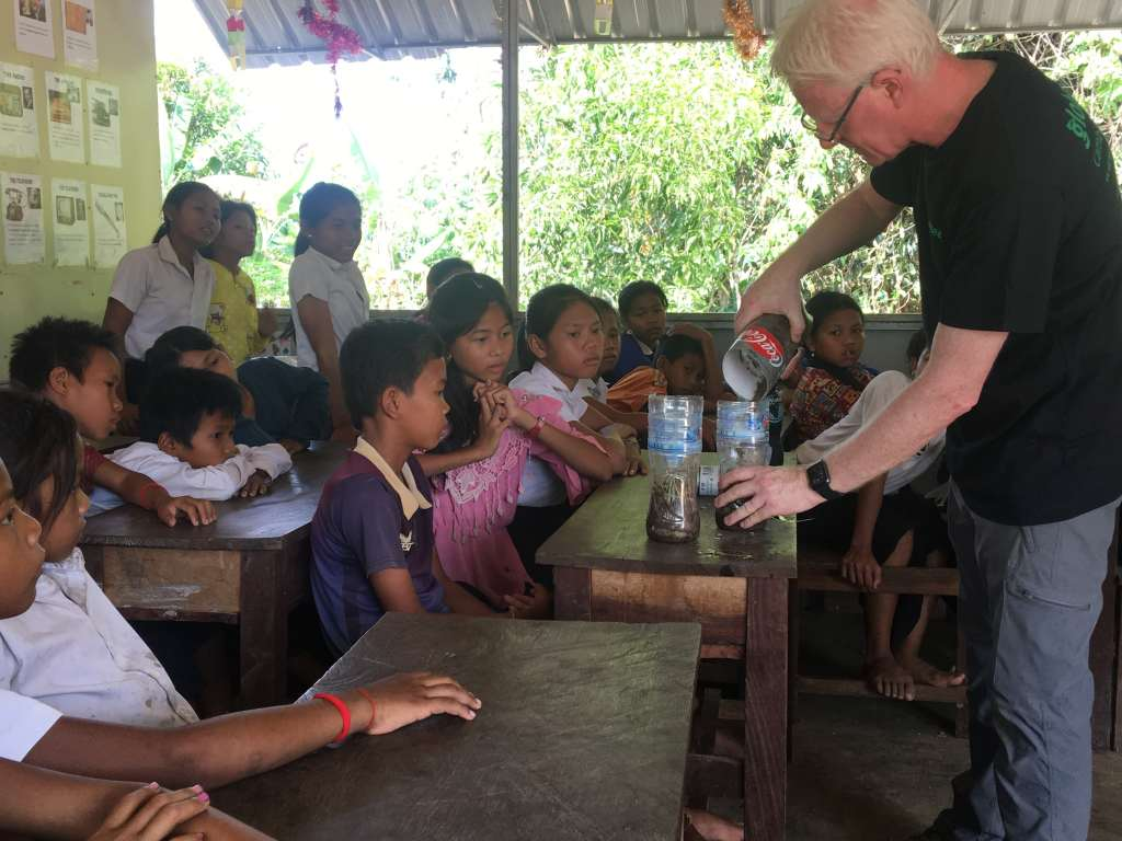 Volunteer showing children how to compost in Cambodia