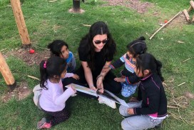 volunteer reading with students at kids community project in Cusco Peru