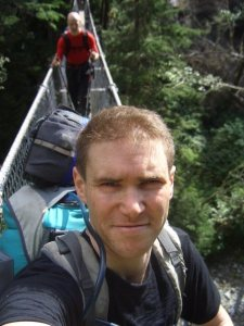 Global Therapies: Tim crossing a bridge on West Coast Trail, Vancouver Island, Canada