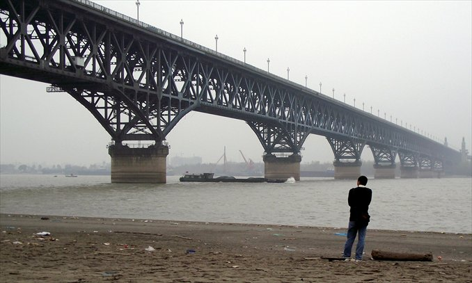 A man watches the Nanjing Yangtze River Bridge from a bank in Nanjing, Jiangsu Province. Photo: IC
