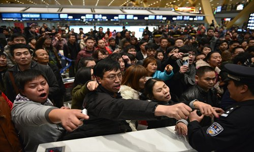 Stranded passengers vent their anger at a check-in counter of China Eastern Airlines at the Changshui International Airport in Kunming, Yunnan Province Friday, after a dense fog grounded 440 flights on Thursday. Photo: CFP