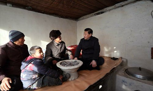 Xi Jinping (R), general secretary of the Communist Party of China (CPC) Central Committee and chairman of the CPC Central Military Commission, visits the family of Tang Rongbin, an impoverished villager in the Luotuowan Village of Longquanguan Township, Fuping County, north China's Hebei Province. Xi made a tour to impoverished villages in Fuping County from Dec. 29 to 30, 2012. Photo: Xinhua