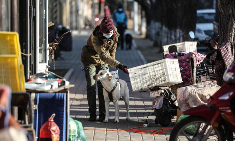 Trainer Wang Lin trains a guide dog on a street in Dalian, northeast China's Liaoning Province, Jan. 14, 2020.Photo:Xinhua