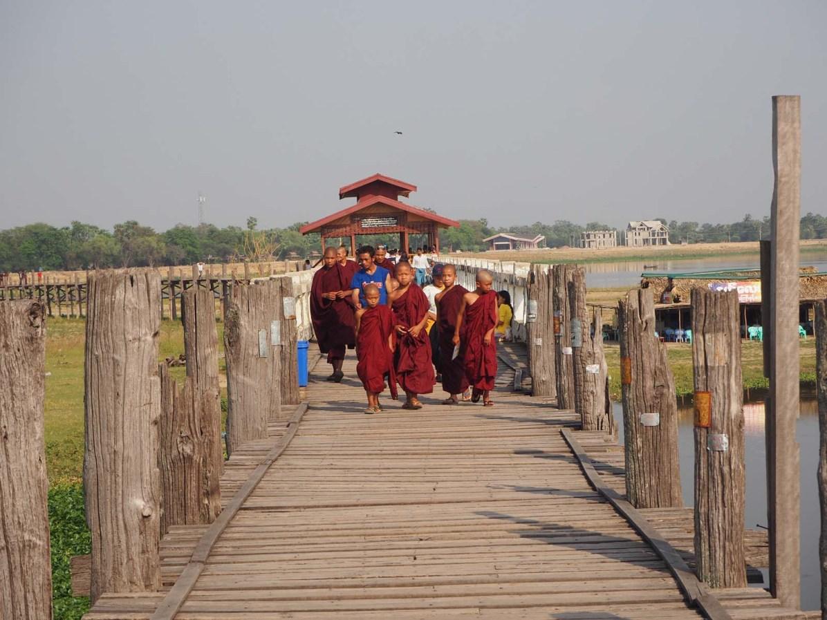 Mönche schreiten über die längste Teakholz-Brücke der Welt (U-Bein-Brücke).