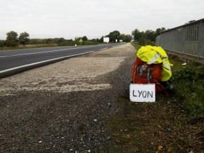 Sac à dos, veste haute-visibilité jaune fluo et pancarte d'auto-stop à destination de Lyon