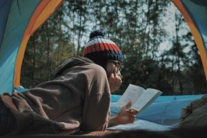 youth reading in tent outdoors - Reading in Nature