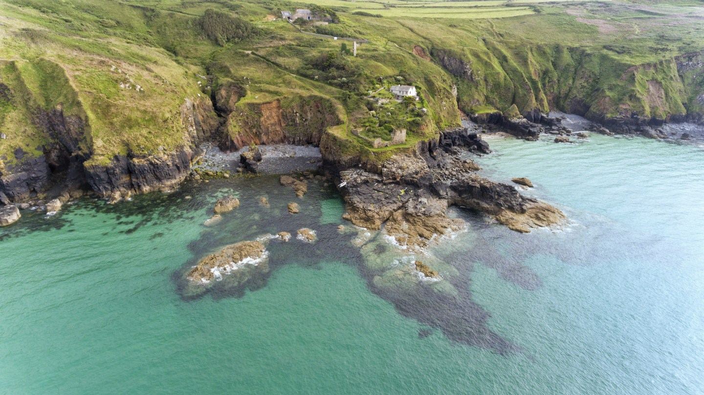 Aerial view of Cornish coastline with high cliffs, rocky shore, stone beaches, coastal footpaths near St Ives, Cornwall, south west England, on a cloudy summer day .