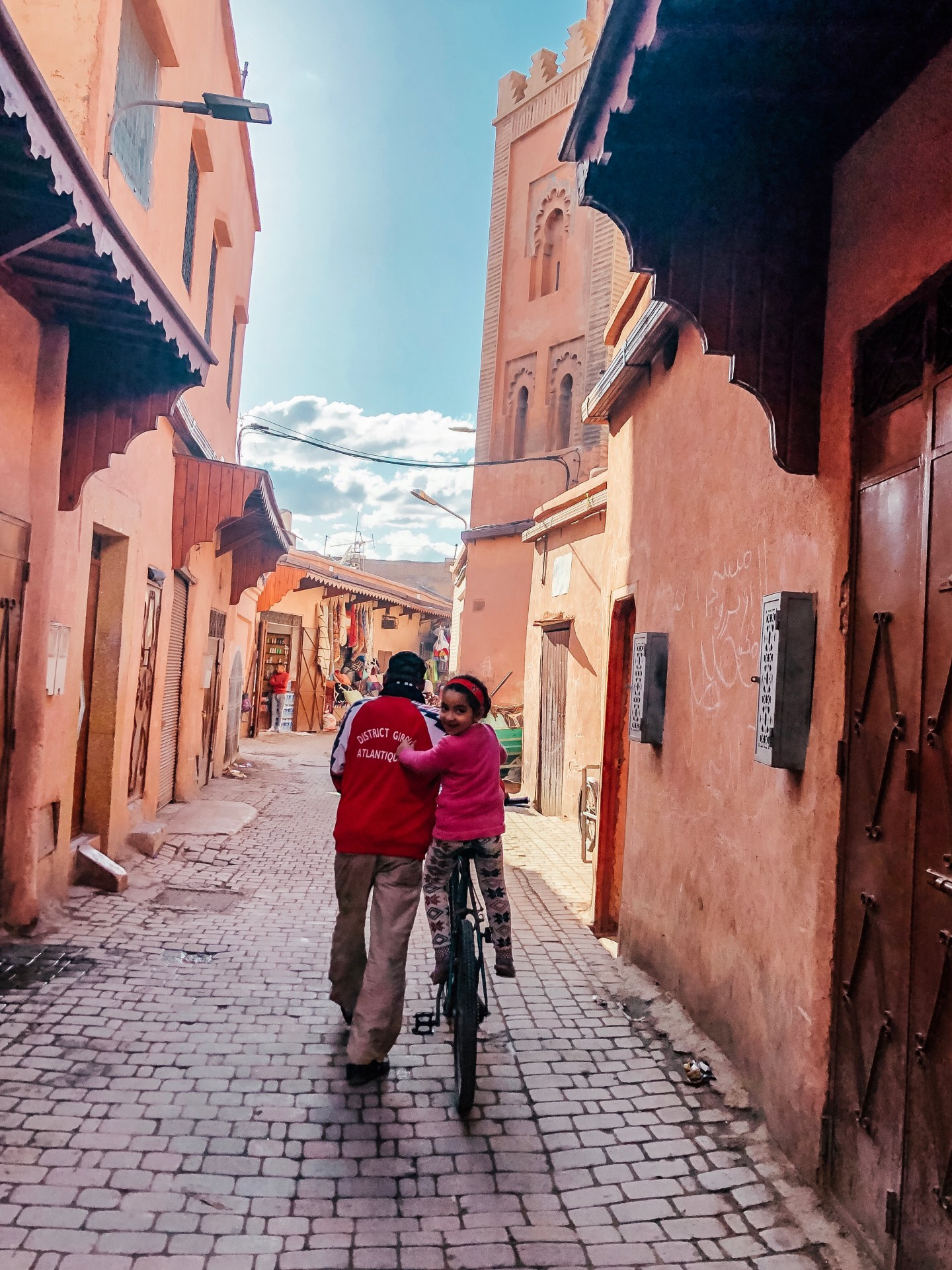 A sweet little girl biking through the Old City with her Dad