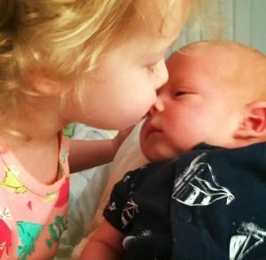 child kissing newborn