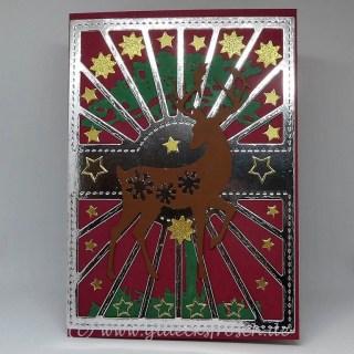rote Weihnachtkarte mit Hirsch und Sterne und Baum und silberfarbenem Hintergrund