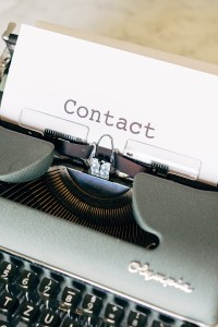 Contact is on a piece of paper in a typewriter.