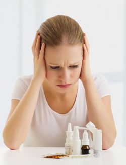 woman with a headache and flu and with medicines