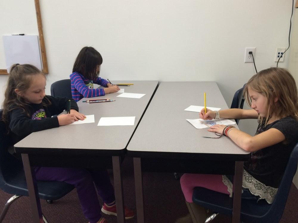 medium resolution of students coloring photos of a menorah