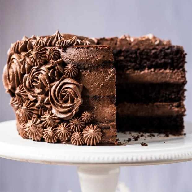 Sliced paleo & keto chocolate cake with cream cheese buttercream frosting