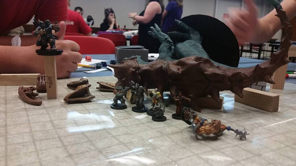 Posting with the body of the defeated Tarrasque, the bodies of their fallen comrades, and the illusion of a giant still fighting in the background.