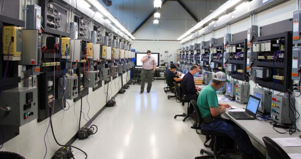 Cody Brewer (center), GNTC's Instrumentation and Controls instructor, watches over the PLC trainees during an evening continuing education session.