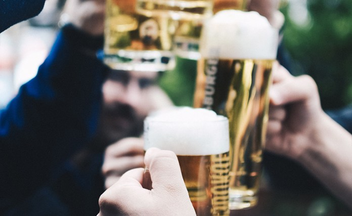 Close up of beer glasses toasting