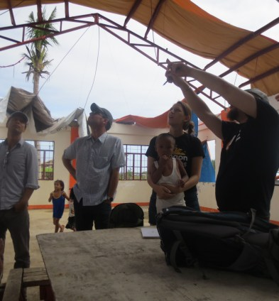 Jacob and Eric explaining the roof repairs to Elsa - GoAbroad Foundation Director