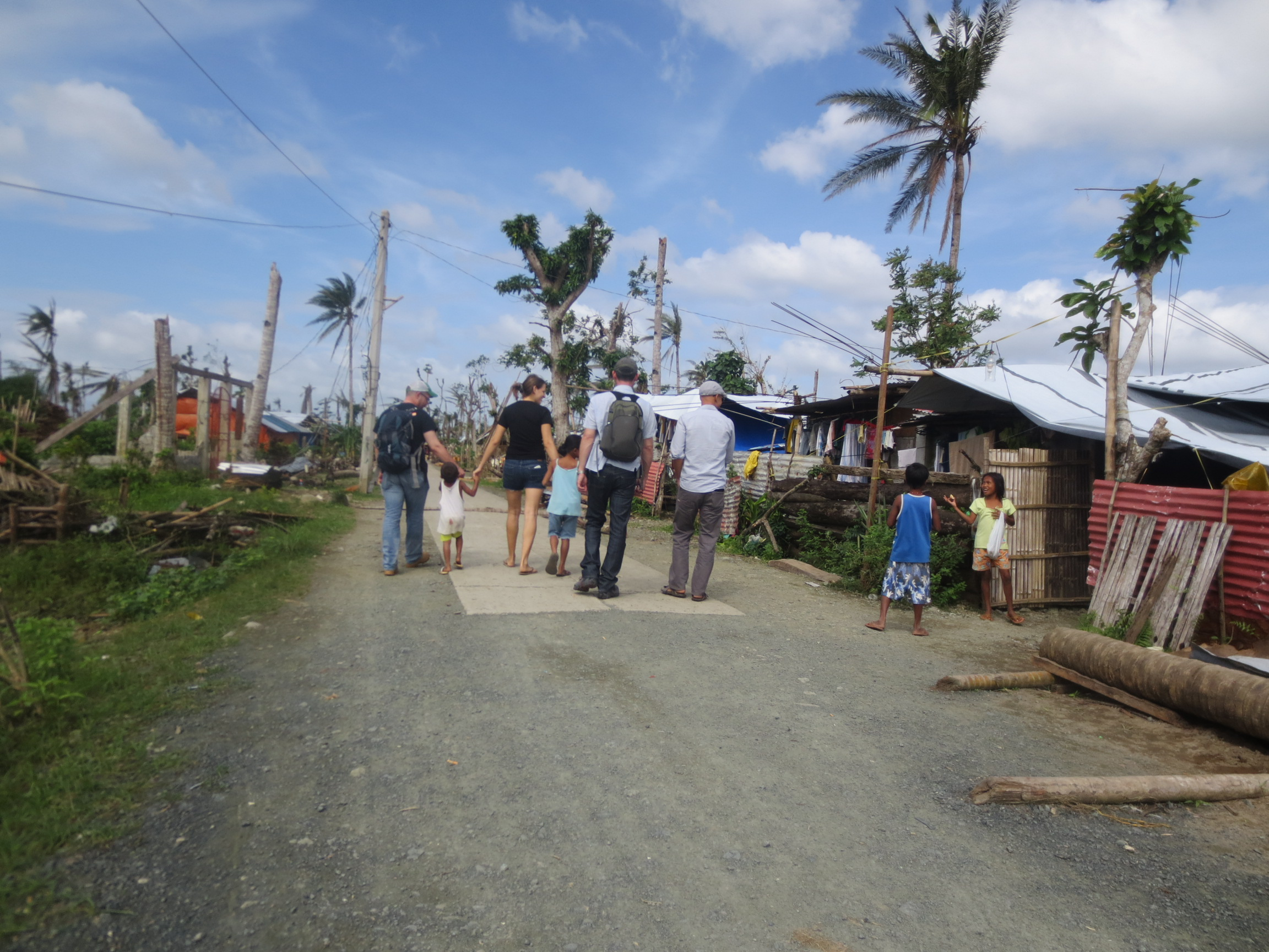 Eric (far left) with Elsa and the children in Cangumbang assessing the damage to the village