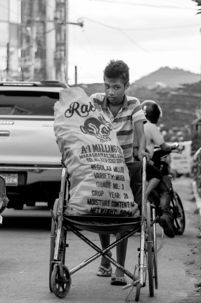 """""""PWD - person with determination"""" - A mentally disabled boy gathers plastic bottles with his wheelchair. Photo Credit: Vic Gloria"""