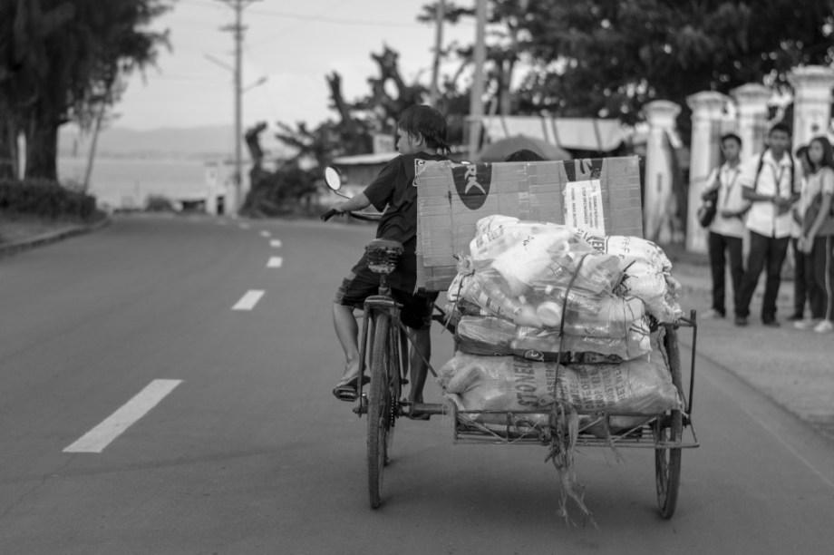 """balun mo patung ko"" - Young boy loads collected bottles and cartons on his pedicab to be sold at junkshop. Photo Credit: Vic Gloria"