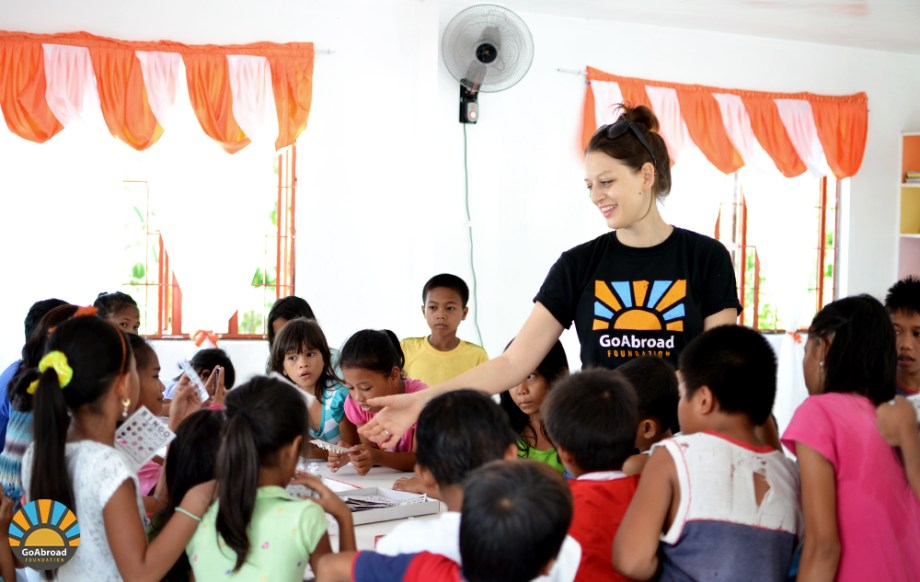 A volunteer playing Bingo with kids