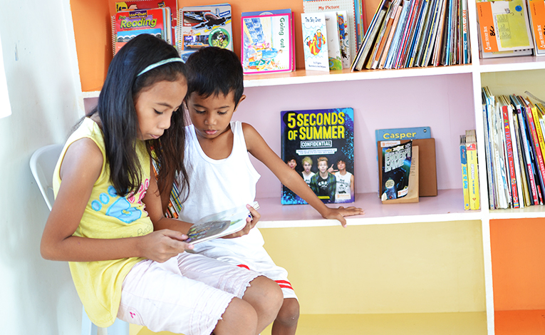 Filipino kids reaching a book
