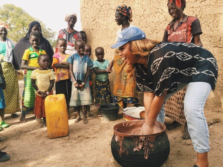 Volunteer cleaning a pot in Burkina Faso