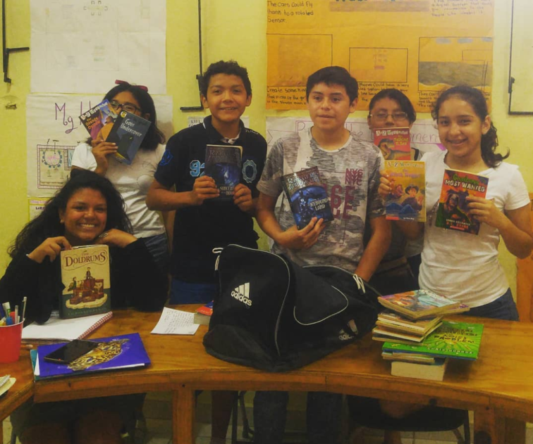 students holding up books