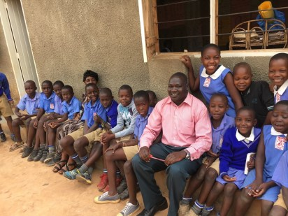 Ugandan teacher with students
