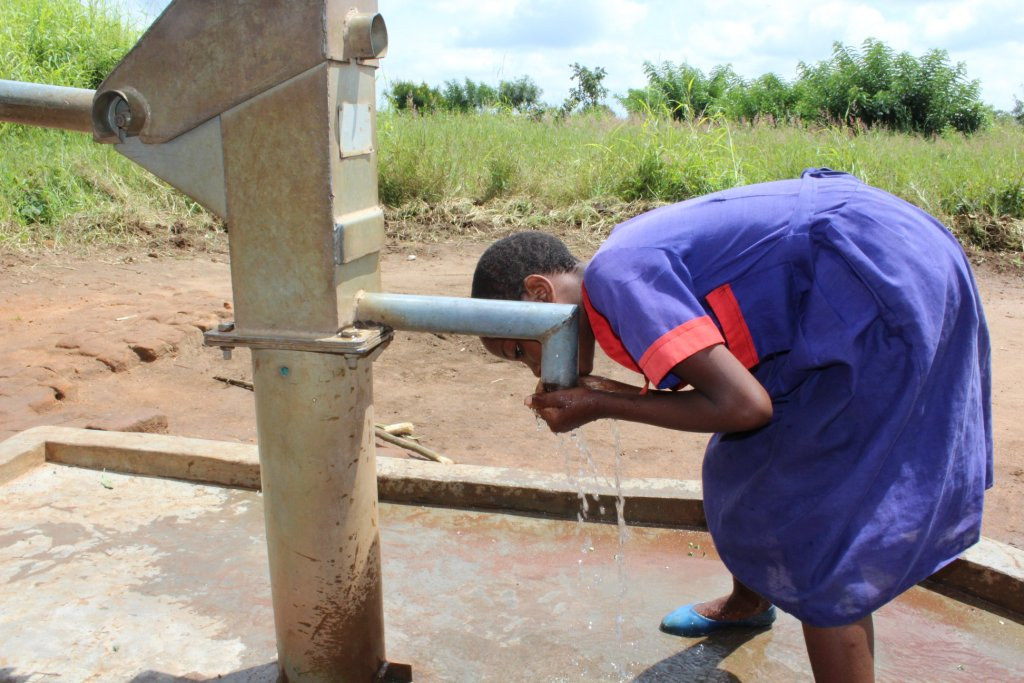 A young girl drinking from a tap of a well