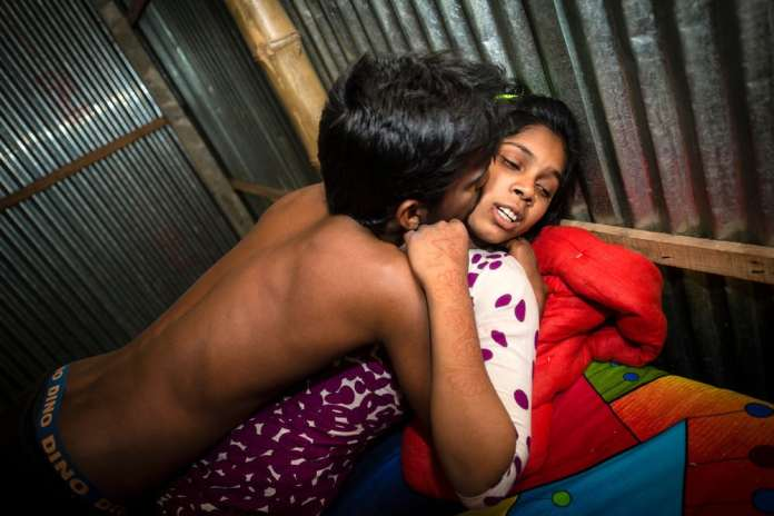 Pakhi, 15 years old, is with a customer in her room. She has lived there since she was 14. She was married at age 12 but then ran away. A man picked her up from the street and sold her into the brothel. © Sandra Hoyn. Finalist, LensCulture Portrait Awards 2016