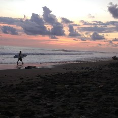 Surfer walking on Costa Rican beach at sunset