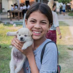 Young girl holding a puppy and smiling