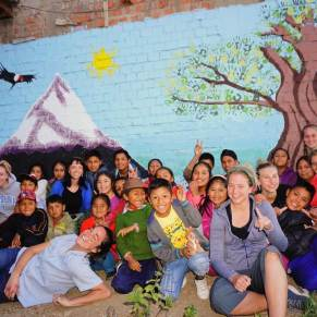 Students and volunteers in Peru posing for a group photo in front of a mural