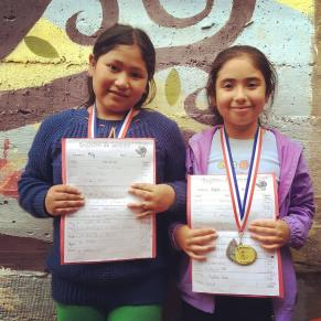 2 young girls with their homework awards
