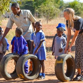 Young children and volunteers playing with tires