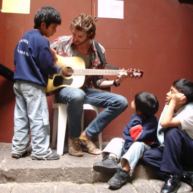 Volunteer playing guitar for children