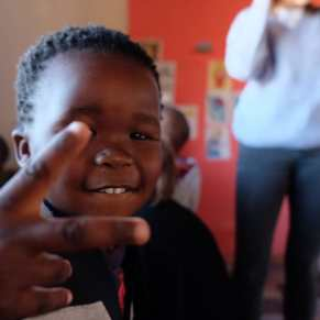 Young boy giving peace sign