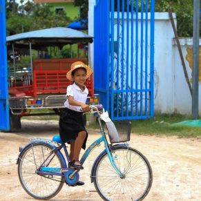 Young girl on a blue bicycle